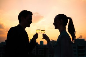 Young couple celebrating with glass of wine in the city.